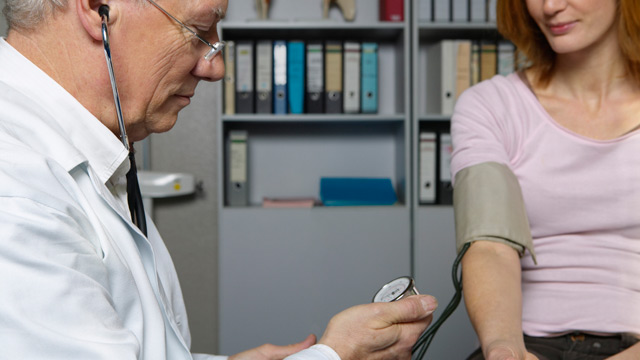 PHOTO: Doctor checking womans blood pressure