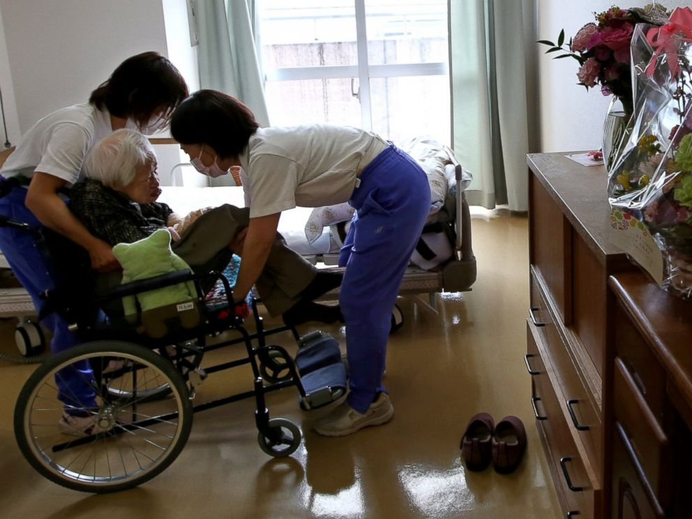 PHOTO: Nursing home staff help Misao Okawa, the worlds oldest Japanese woman, get into bed after lunch on her 117th birthday at Kurenai Nursing Home on March 5, 2015 in Osaka, Japan.