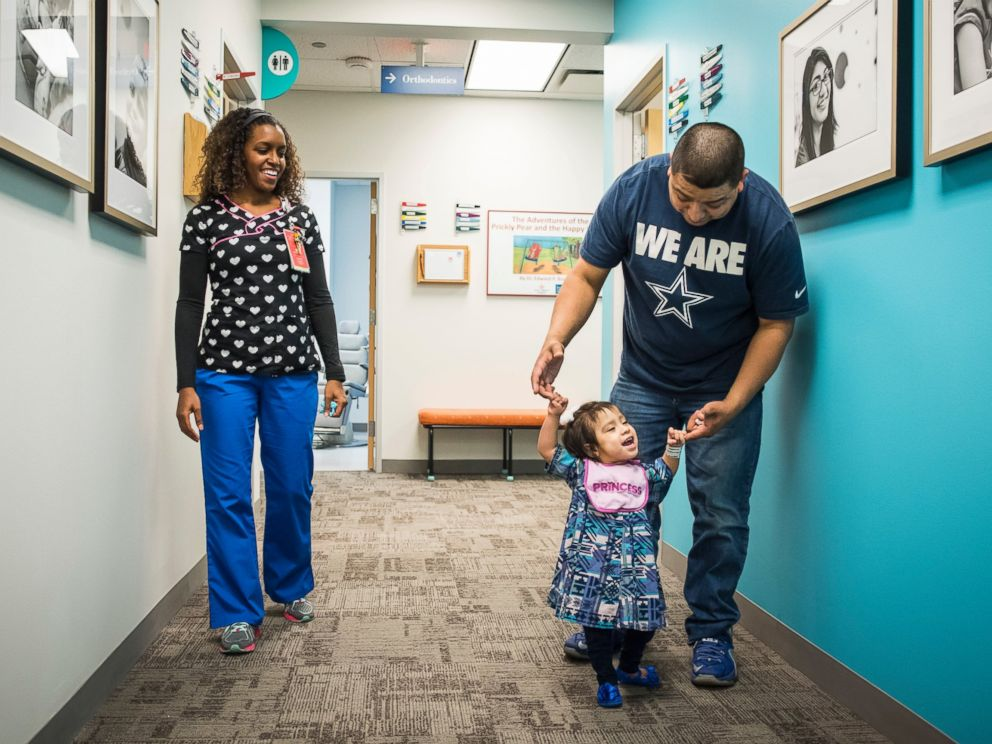 Eric Mata holds daughter Knatalyes hands as she walks down the hall of a clinic at Texas Childrens Hospital.