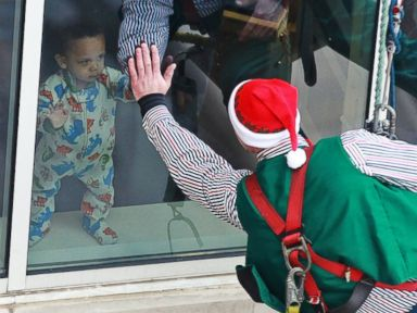 PHOTO: A toddler high-fives one of the elves through the window.