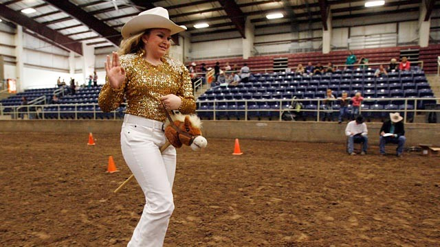 PHOTO:&nbsp;Jaclynn Brooks smiles and waves as she rides her stick horse.