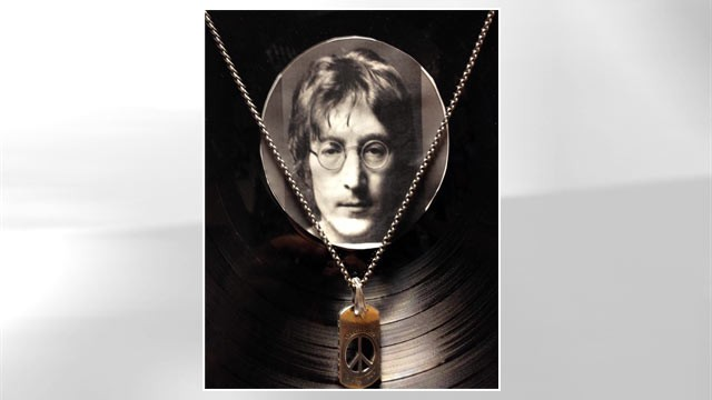 PHOTO: A pendant with a piece of John Lennon's tooth in front of vinyl at the Castlepark Dental Centre in northeast England.