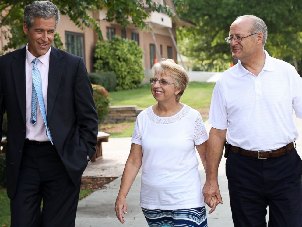 PHOTO: Dr. Richard Besser walks with Ebola survivor Nancy Writebol and her husband, David.