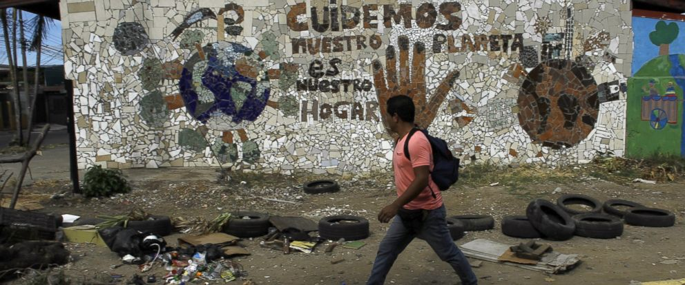 PHOTO: A man walks past garbage in the Pavas neighbourhood near San Jose, Costa Rica Feb. 9, 2016.