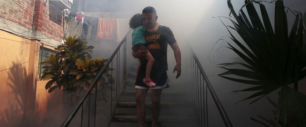 PHOTO: A man walks away from his home with his son as health workers fumigate the Altos del Cerro neighborhood as part of preventive measures against the Zika virus and other mosquito-borne diseases in Soyapango, El Salvador, Jan. 21, 2016.