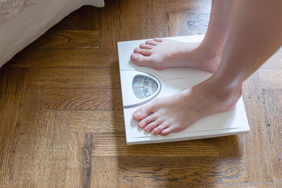 PHOTO: A woman checks here weight on a bathroom scale in this undated stock photo.
