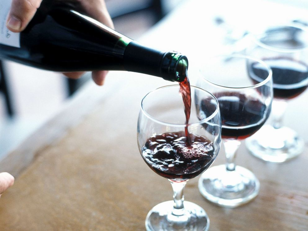 PHOTO: A person is pictured pouring red wine.
