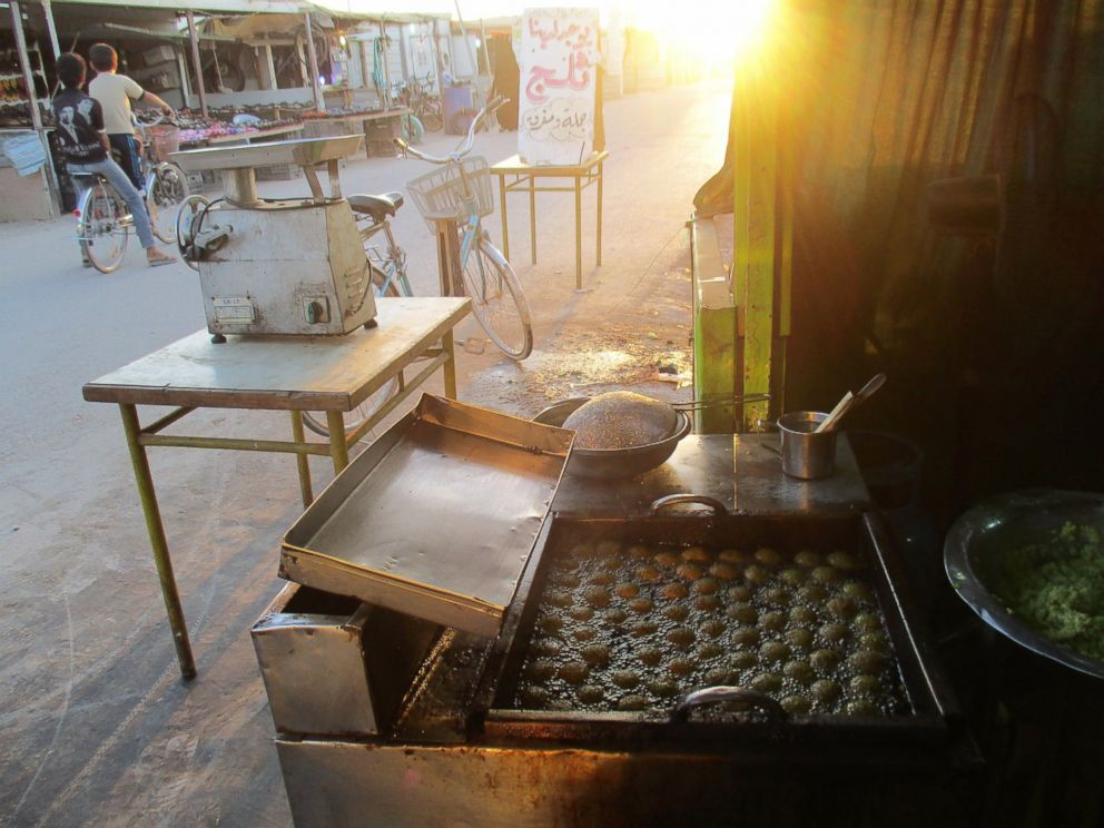PHOTO: The falafel fryer and the beauty of food with the rays of sunlight shown through the mosque minaret at dusk. It gives me hope for a better life someday.