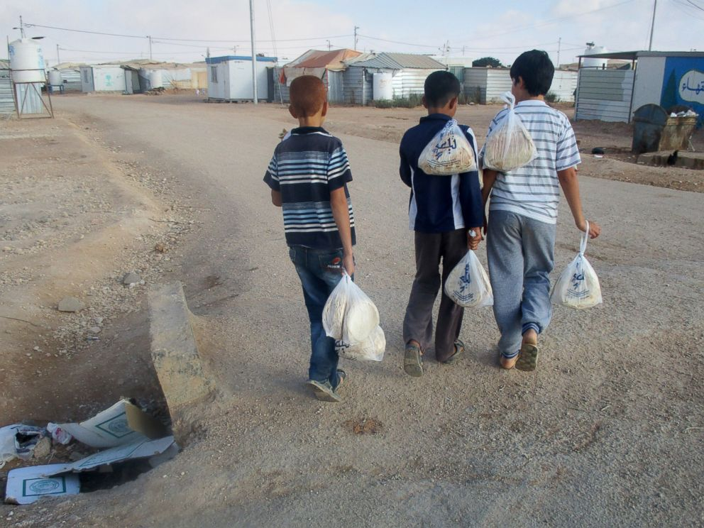 PHOTO: Children carry bread home. We go to the WFP center every morning around 7 a.m. to get bread.