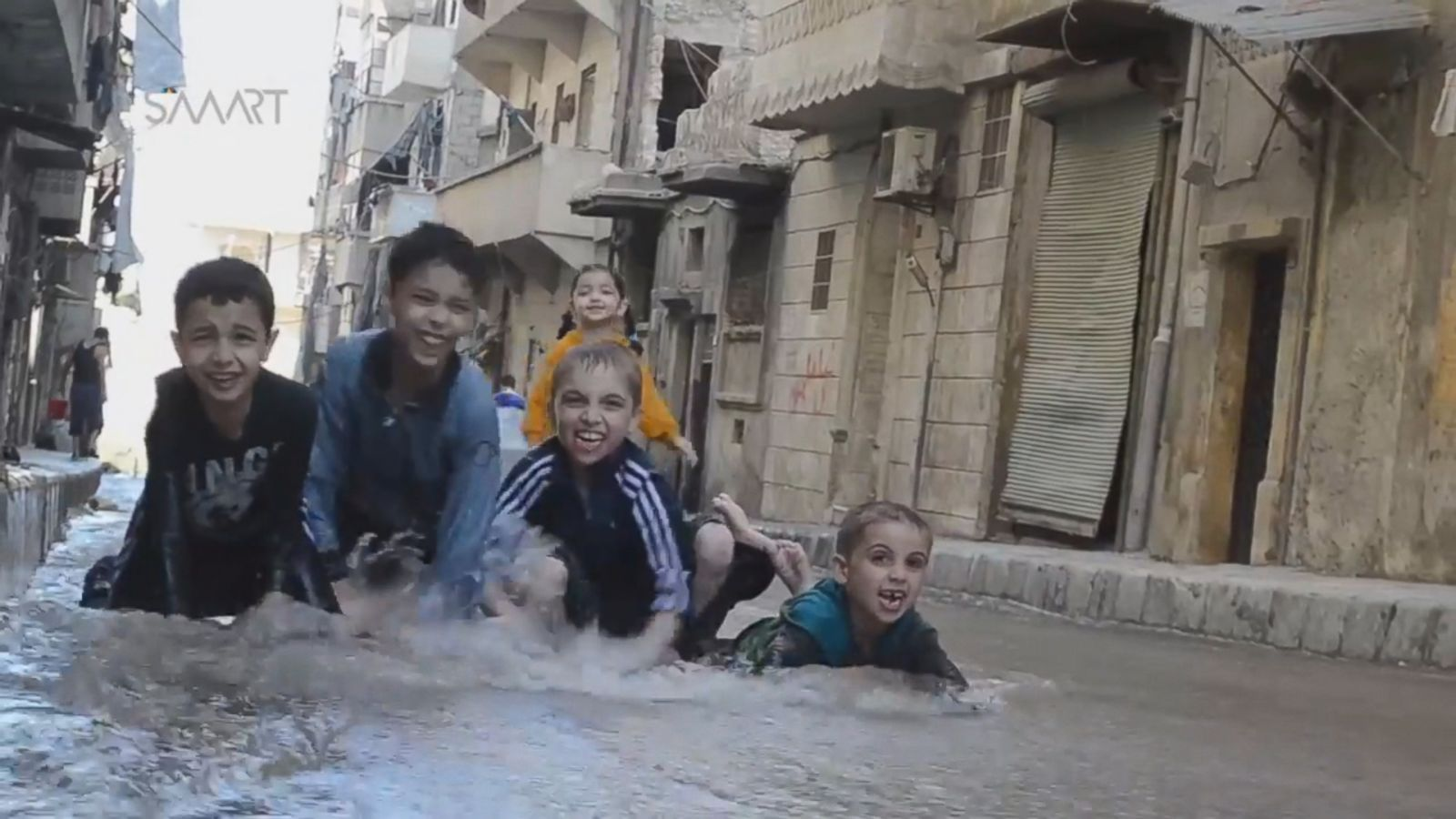 Aleppo children splashed about in water gushing down streets in the rebel-held neighborhood Mashhad on Thursday, Sept. 29, after airstrikes damaged a water main there.