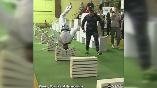Sixteen-year-old Bosnian taekwondo martial artist smashes 111 building blocks in 35 seconds with his head in front of a cheering crowd.