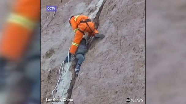 Firefighters partake in dangerous rescue mission to save young boy who got caught in the crevice of a cliff after falling off the edge in China.
