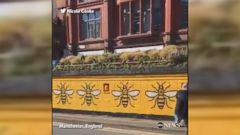 Man paints worker bees - one of the symbols of the city of Manchester - on a wall at Manchesters Stevenson Square while dozens of people wait outside of a tattoo parlor to get bee tattoos for charity.