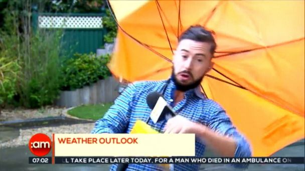 VIDEO: Deric Hartigan quickly recovered from being hit by a gust of wind that left his colleagues laughing.