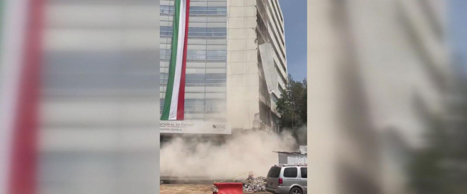 Part of a building's outer wall can be seen falling to the ground after Tuesday's earthquake.