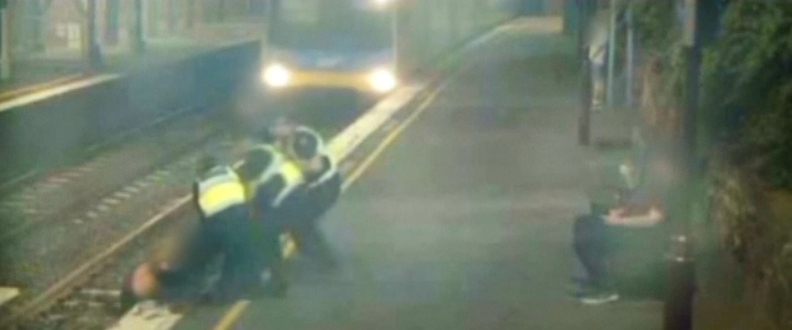 Three police officers rushed to pull her to safety just seconds before the train would have hit her.