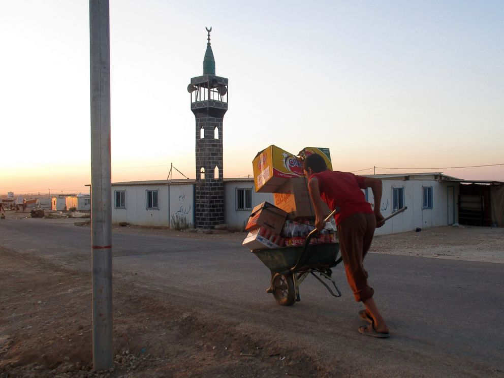 PHOTO: A boy about my age transports items on a wheelbarrow past the mosque.