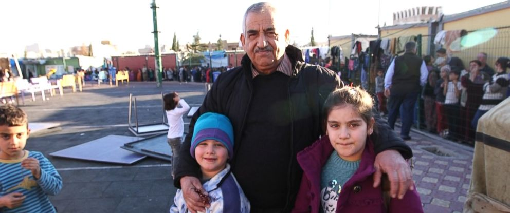 Nissan Butrus, pictured with his grandchildren, is a retired pharmacist who fled Qaraqosh with his family of 10 packed in the back of a truck.