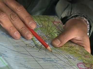 PHOTO: Members of the planes search team check map locations during the flight.
