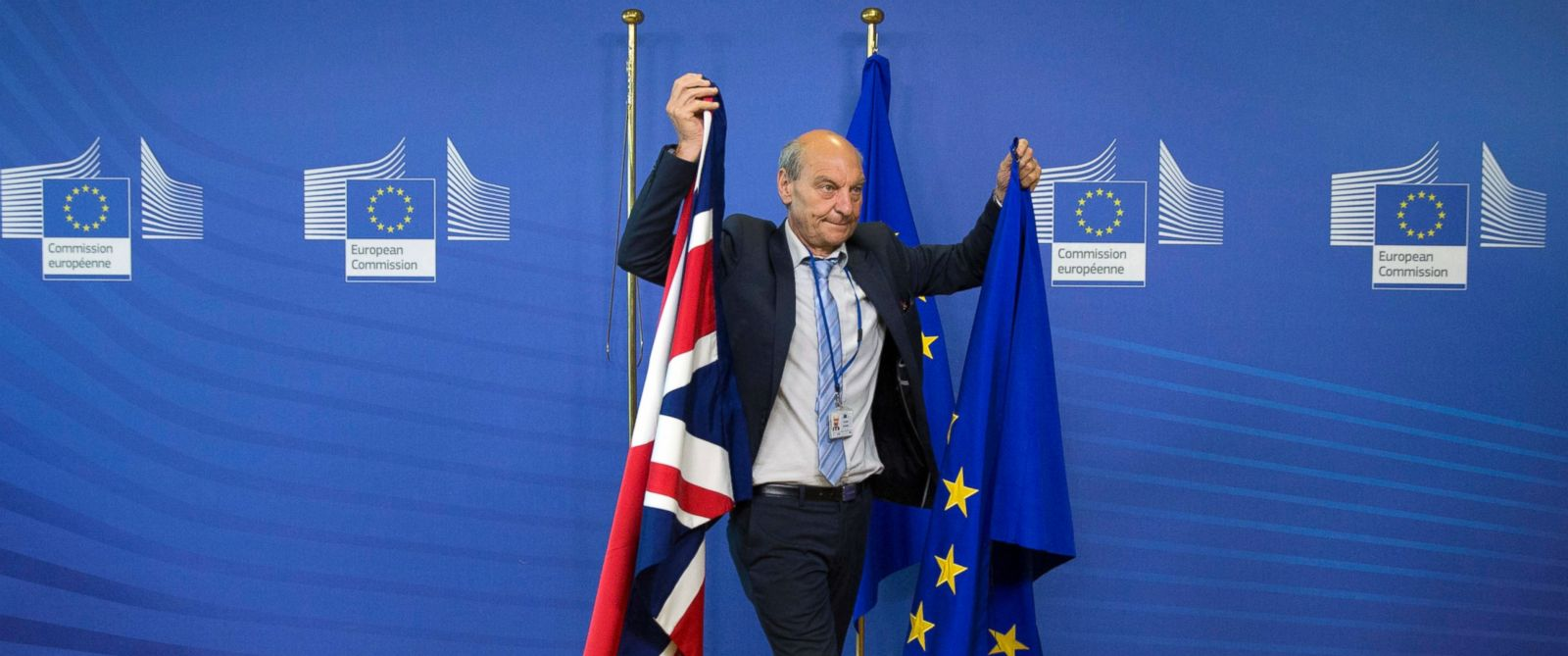 PHOTO: A member of protocol changes the EU and British flags prior to the arrival of EU Chief Brexit Negotiator Michel Barnier and British Secretary of State David Davis at EU headquarters in Brussels, June 19, 2017.