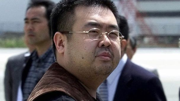 A man believed to be Kim Jong Nam, the eldest son of then North Korean leader Kim Jong II, looks at a battery of photographers as he exits a police van to board a plane to Beijing at Narita international airport in Narita, northeast of Tokyo, May 4, 2001.