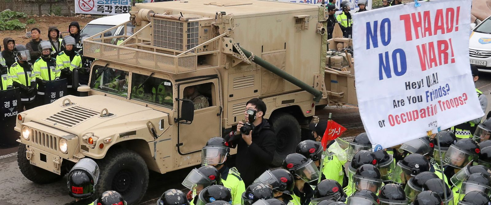 PHOTO: U.S. military vehicle moves past banners opposing a plan to deploy an advanced U.S. missile defense system called Terminal High-Altitude Area Defense, as South Korean police officers stand guard in Seongju, South Korea, on April 26, 2017.