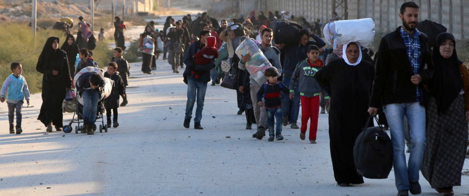 PHOTO: This photo provided by the Rumaf, shows people fleeing rebel-held eastern neighborhoods of Aleppo into the Sheikh Maqsoud area that is controlled by Kurdish fighters, Syria, Nov. 27, 2016.
