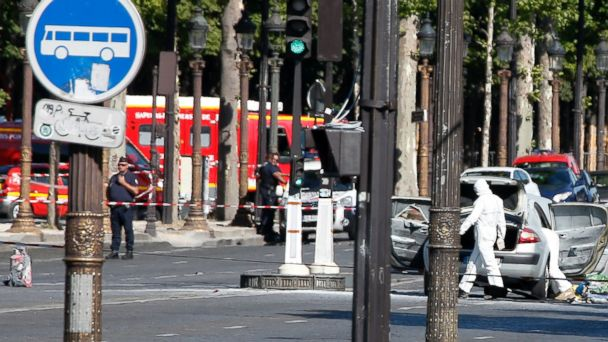 PHOTO: Scientific police officers investigate on the suspected car, right, after a man rammed into a police convoy on the Champs Elysees avenue in Paris, June 19, 2017.