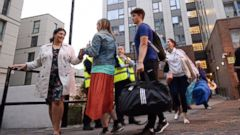"PHOTO: Residents leave a tower block on the Chalcots Estate in Camden, London, June 23, 2017, as the building is evacuated in the wake of the Grenfell Tower fire to allow ""urgent fire safety works"" to take place."