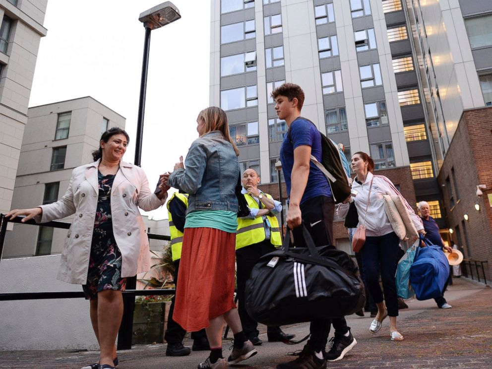 PHOTO: Residents leave a tower block on the Chalcots Estate in Camden, London, June 23, 2017, as the building is evacuated in the wake of the Grenfell Tower fire to allow urgent fire safety works to take place.