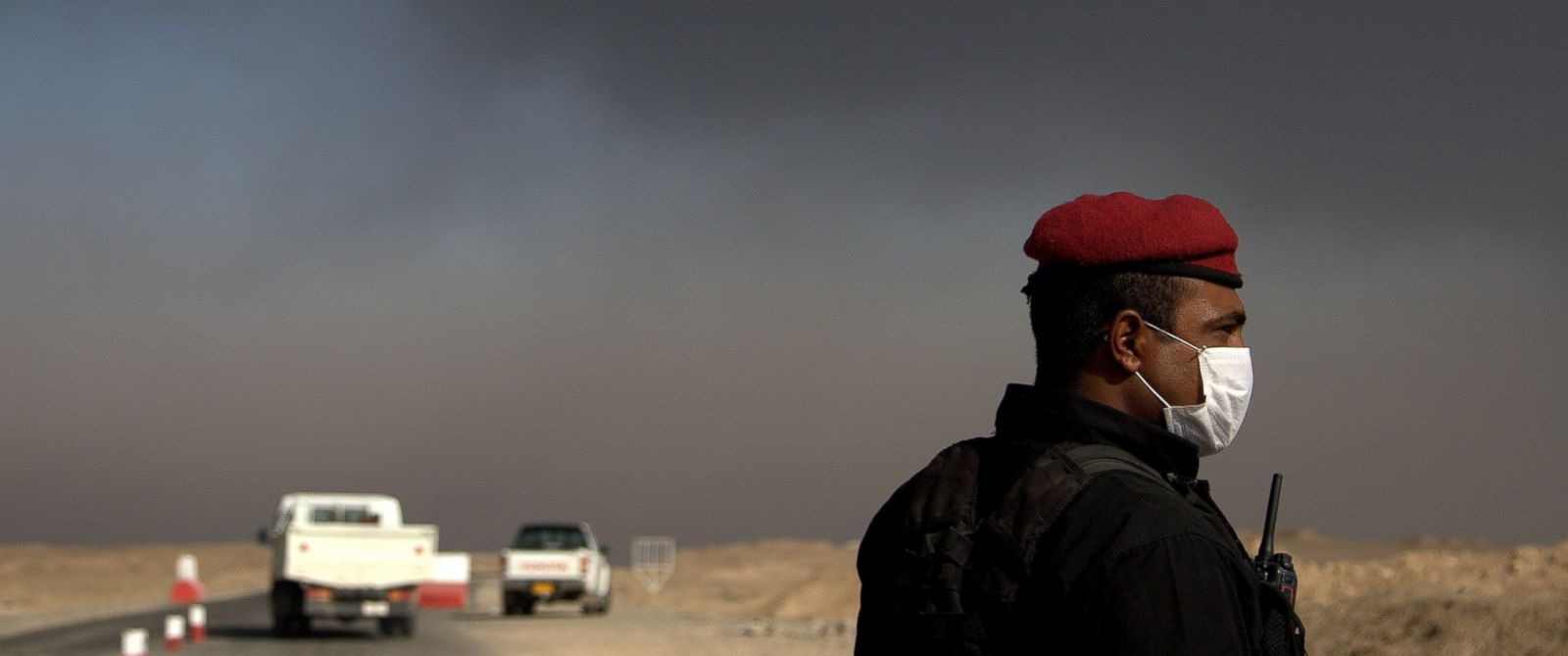 A member of the Iraqi special forces guards a checkpoint near the village of Awsaja, Iraq, as smoke from fires lit by Islamic State militants at oil wells and a sulfur plant fill the air, Oct. 22, 2016.