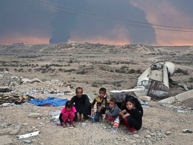 PHOTO: Internally displaced persons sit at a checkpoint as smoke rises from the burning oil wells in Qayyarah, about 31 miles (50 km) south of Mosul, Iraq, Oct. 23, 2016.