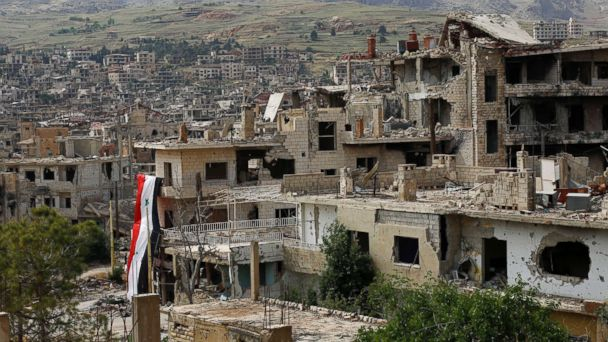 PHOTO: A Syrian National flag hangs out of a damaged building at the mountain resort town of Zabadani in the Damascus countryside, Syria, May 18, 2017.