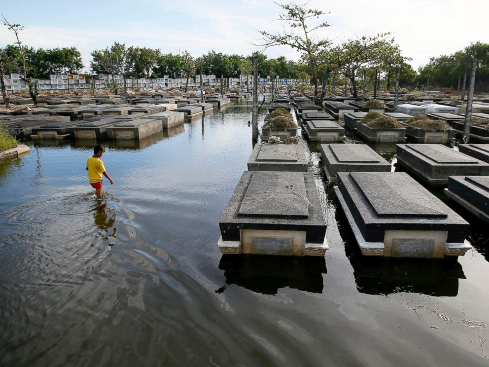 PHOTO: A boy wades through a flooded cemetery as the country prepares for the traditional honoring of the departed every Nov. 1 known as All Saints Day, at Masantol township north of Manila, Philippines Oct. 26, 2016.