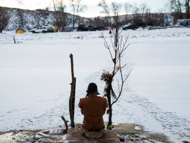 PHOTO: Army veteran Nick Biernacki, of Indiana, prays at Cannonball River at the Oceti Sakowin camp where people have gathered to protest the Dakota Access oil pipeline in Cannon Ball, N.D., Dec. 4, 2016.