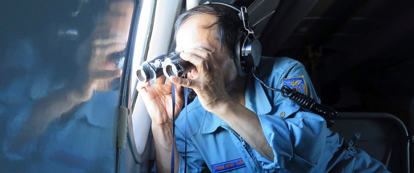 PHOTO: Vietnamese Air Force Col. Pham Minh Tuan uses binoculars on board a flying aircraft during a mission to search for the missing Malaysia Airlines flight MH370 in the Gulf of Thailand, Thursday, March 13, 2014.