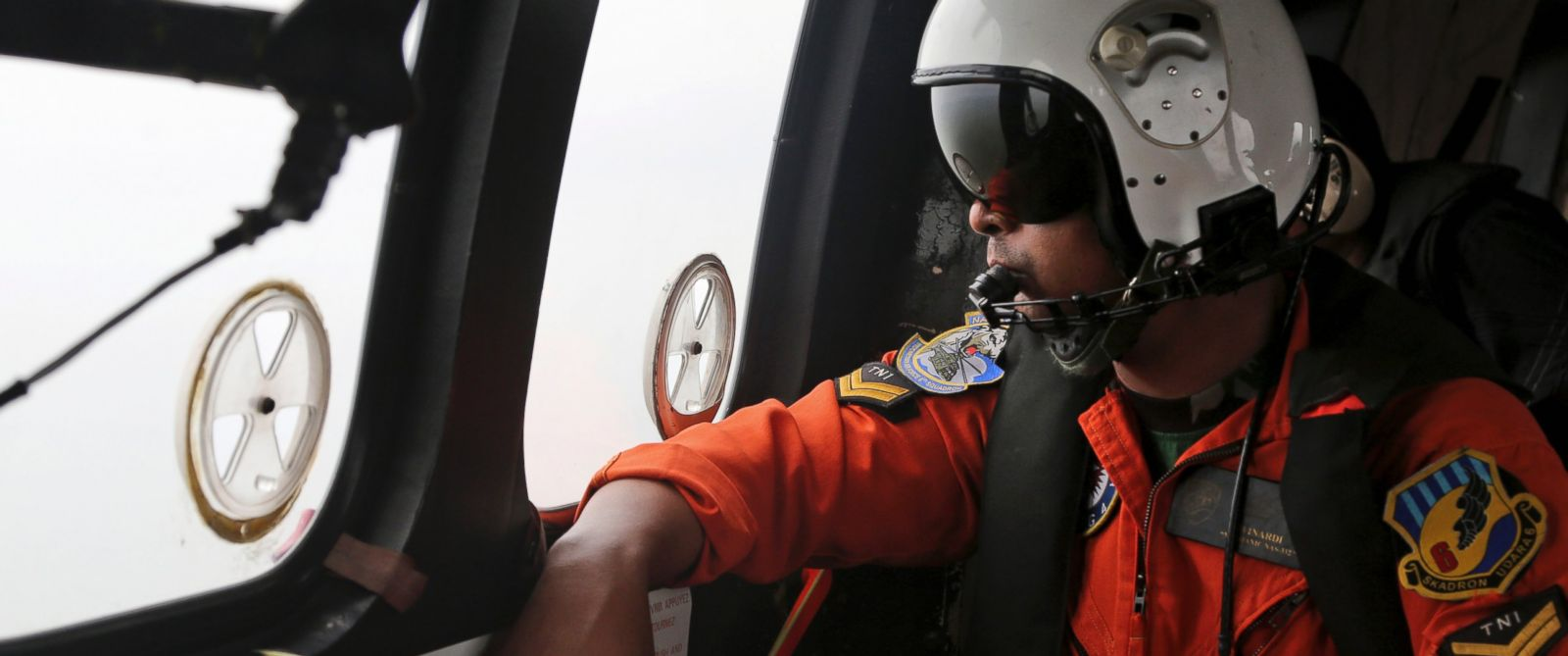 PHOTO: A crew member of Indonesian Air Force NAS 332 Super Puma helicopter, looks out of the windows during a search operation for the victims and wreckage of AirAsia Flight QZ 8501 over the Java Sea, Indonesia, Jan. 5, 2015.