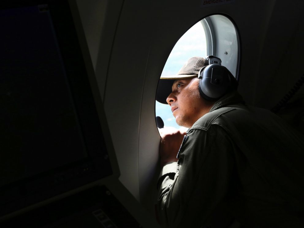 PHOTO: A crew member of Indonesian Navy CN-235 airplane looks out of the window during a search operation for the missing AirAsia flight 8501 over the waters off Bangka Island, Indonesia, Dec. 30, 2014.