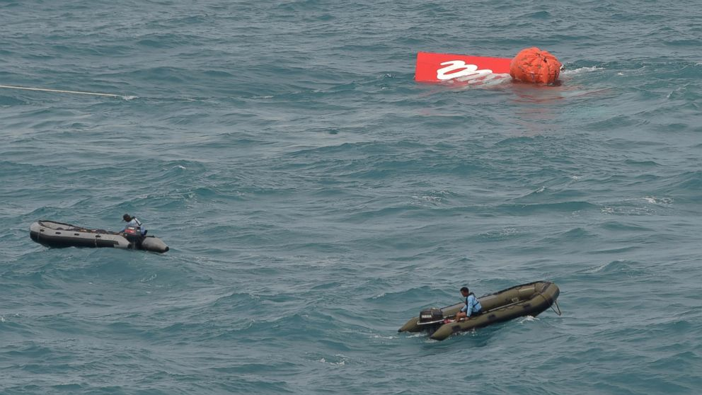 PHOTO: A portion of the tail of AirAsia Flight 8501 is seen floating on the water as Indonesian navy divers conduct search operations for the black boxes of the crashed plane in the Java Sea, Indonesia, Jan. 10, 2015.