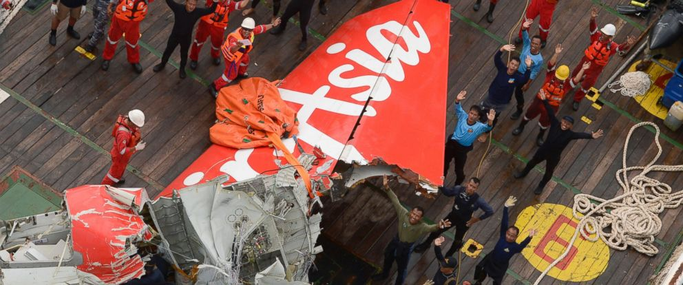 Rescuers wave at an Indonesian Air Force helicopter near portion of AirAsia Flight 8501 after it was recovered from the sea floor on the deck of a rescue ship on the Java Sea, Saturday, Jan. 10, 2015.