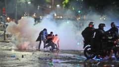 PHOTO: Soccer fans try to escape from a tear gas cloud and a police water cannon at a rally after Argentinas performance in a 1-0 loss to Germany in the World Cup finals, Sunday, July 13, 2014, in Buenos Aires, Argentina.