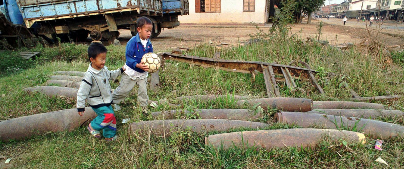 PHOTO: Two Laotian boys play with their ball in a front yard near collected bomb canisters in Xiangkhouang, Laos, in this Nov. 11, 1997 file photo.