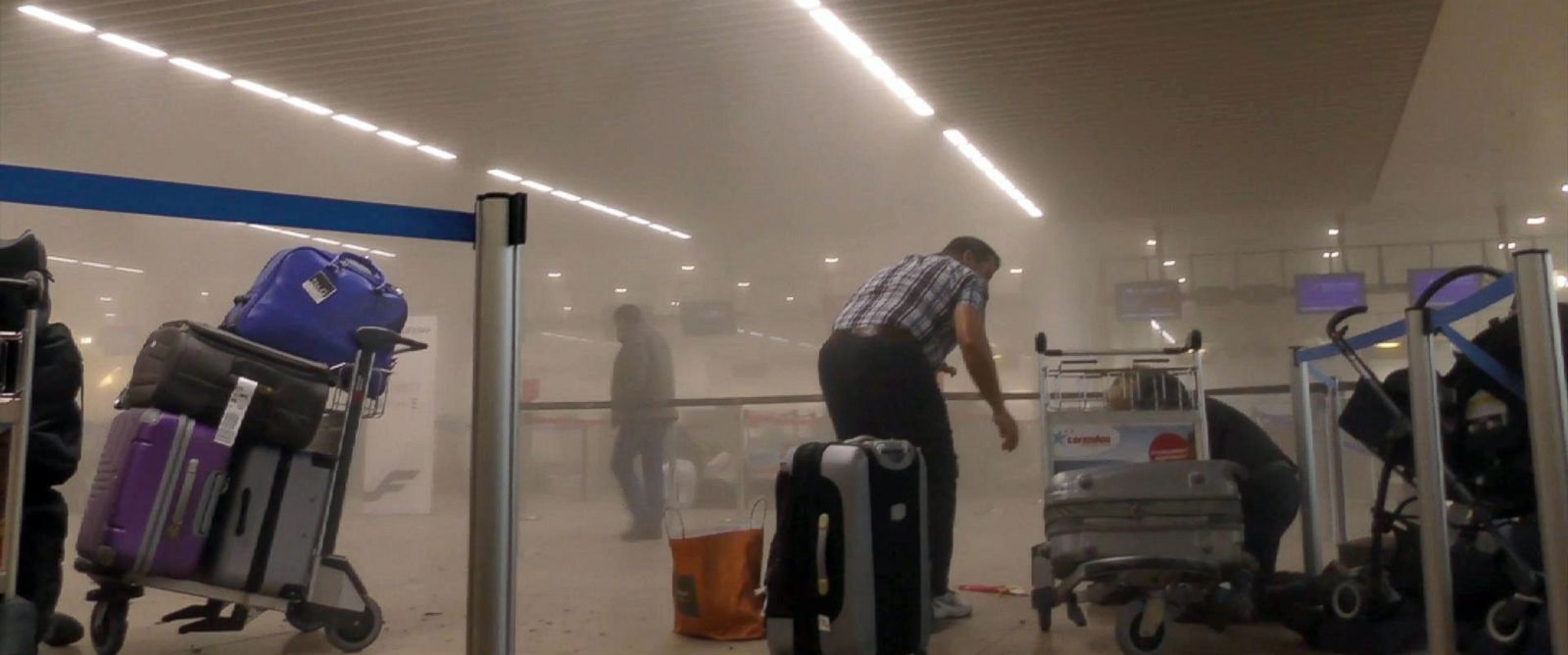 PHOTO: Travelers stand in a smoke filled terminal at Brussels Airport, in Brussels after explosions, March 22, 2016.