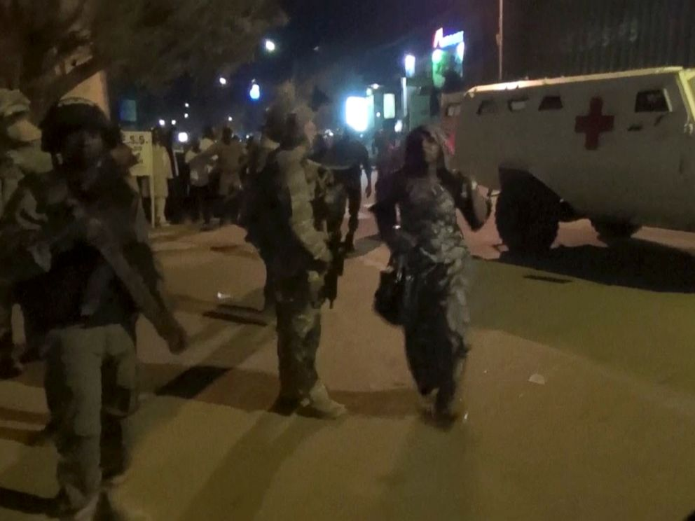 PHOTO: In this image taken from video from AP Television, a freed woman, center, walks past French special forces near the Splendid Hotel, early Saturday, Jan. 16, 2016, in Ouagadougou, Burkina Faso.