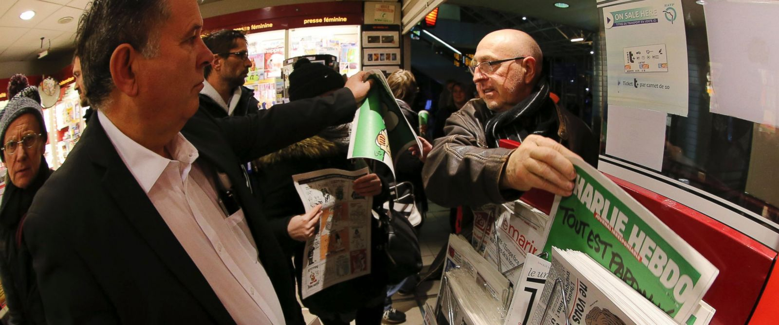 PHOTO: In this photo made with a fish-eye lens, people pick up copies of Charlie Hebdo newspaper at a newsstand in Rennes, western France, Jan. 14, 2015.
