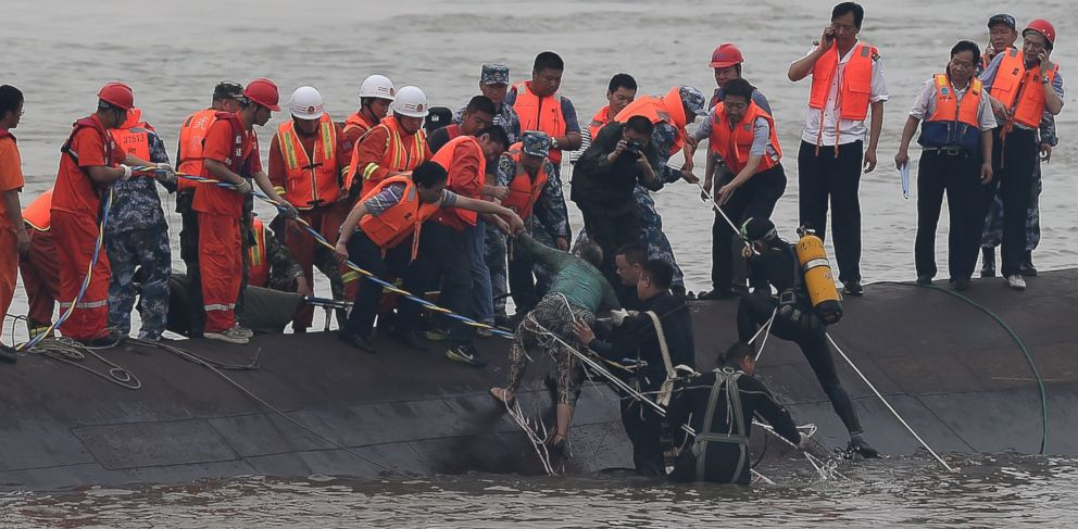 In this photo released by Chinas Xinhua News Agency, rescuers save a survivor, center, from the overturned passenger ship in the Jianli section of the Yangtze River in central Chinas Hubei Province Tuesday, June 2, 2015.