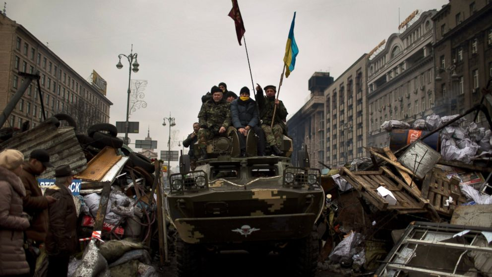 PHOTO: Protesters sit on top of an army armored vehicle along a street in central Kiev, Ukraine, Thursday, Feb. 27, 2014.