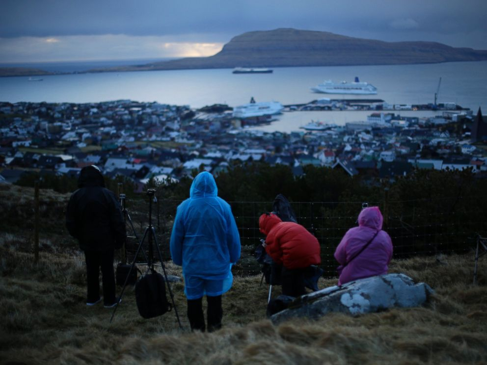 PHOTO: People wait for the start of a total solar eclipse on a hill beside a hotel overlooking the sea and Torshavn, the capital city of the Faeroe Islands, March 20, 2015.
