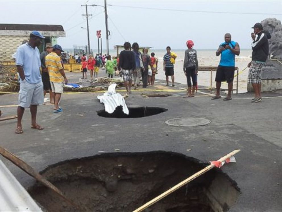 PHOTO: People look at sink holes in the road next to the capitals main market, Aug. 27, 2015, caused by Tropical Storm Erika in Roseau, Dominica.