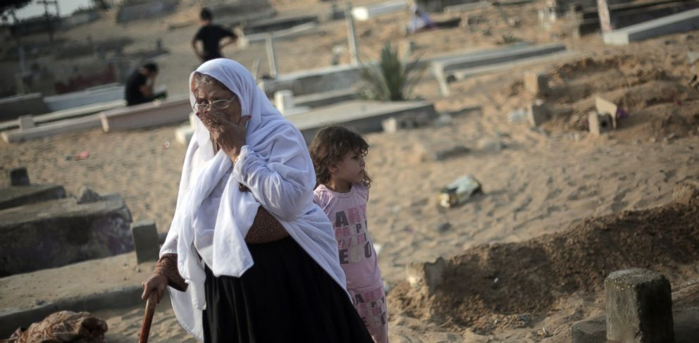 PHOTO: A Palestinian woman visits the graves of relatives marking the first day of Eid al-Fitr in a cemetery in Jabaliya refugee camp, northern Gaza Strip, July 28, 2014.